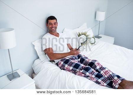 Happy man typing a text message on phone in bedroom