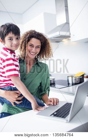 Mother using laptop with son in kitchen at home