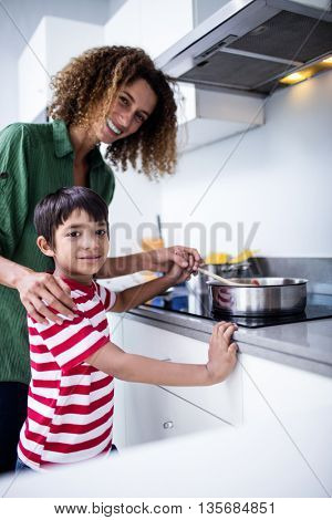 Portrait of mother and son cooking in kitchen at home
