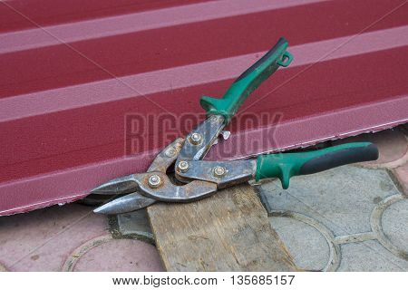 Metal scissors lying near the metal sheets