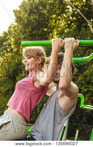 Man And Woman Exercising On Pulldown Outdoor.