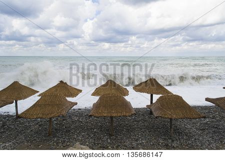 Stone beach with umbrellas in storm time