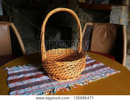 Wicker basket on tablecloth in dark room