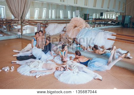 Thr seven ballerinas sitting and lying against ballet rack in the rehearsal hall of the theater