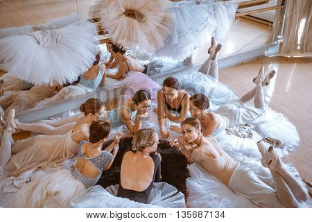 Thr seven ballerinas lying on floor in the rehearsal hall of the theater