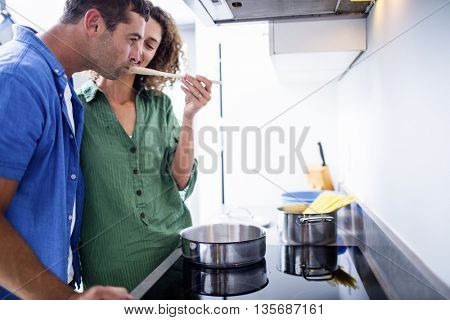 Man tasting food from pot in kitchen