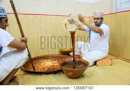 NIZWA, OMAN, MAY 27, 2016: a worker pours freshly made traditional Omani halwa into a wooden pot