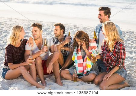 Friends drinking beer at the beach on a sunny day
