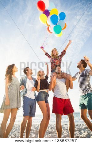 Friends posing with balloon on sand on a sunny day