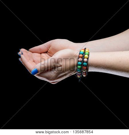 Women's hands with blue nails on a black background