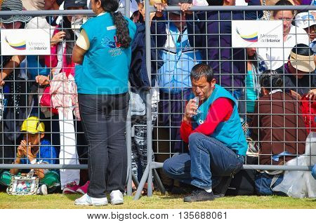 QUITO, ECUADOR - JULY 7, 2015: Volunteers behind the metal mesh guarding people at pope Francisco mass, blue vest.