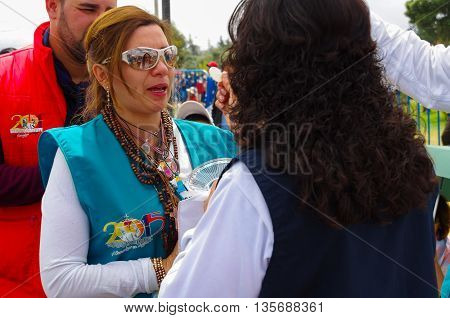 QUITO, ECUADOR - JULY 7, 2015: A volunteer is given the communion to a woman, pope Francisco mass organization.