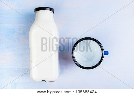 Milk bottle and metal drinking cup on rustic wooden table top view flat lay