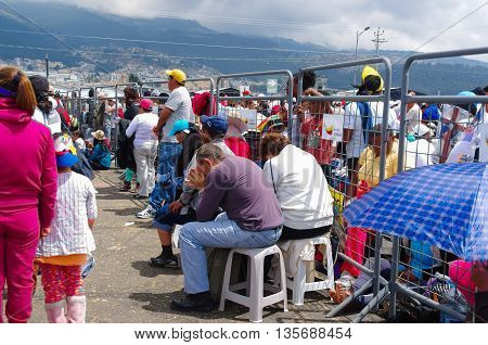 QUITO, ECUADOR - JULY 7, 2015: A couple of mature people sitting in the middle of the mass, praying under the sun.