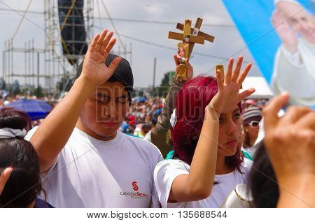QUITO, ECUADOR - JULY 7, 2015: Unidentified people praying, raising her hands and close the eyes to receive blessings.