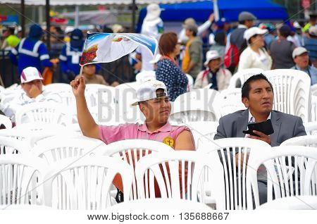 QUITO, ECUADOR - JULY 7, 2015: Two mens sitting on a white chairs waitting for pope Francisco , ass, one of them holding a flag.