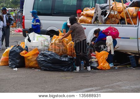 QUITO, ECUADOR - JULY 7, 2015: Garbage cleaners picking up all the trash after the event. Pope Francisco mass.