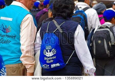 QUITO, ECUADOR - JULY 7, 2015: Two voluntarees walking around pope Francisco mass event, vests and backpacks to identified them.