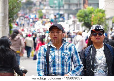 QUITO, ECUADOR - JULY 7, 2015: Two unidentified mens walking in the middle of the event, full of people. Pope Francisco mass.