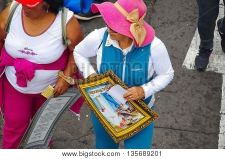 QUITO, ECUADOR - JULY 7, 2015: Unidentified sport woman holding a little poster of pope Francisco on her hands.