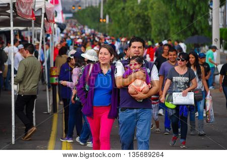 QUITO, ECUADOR - JULY 7, 2015: Family walking on the street, mother, father and little child want to see pope Francisco.