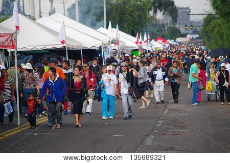 QUITO, ECUADOR - JULY 7, 2015: Long avenue crowded, people walking to see pope Francisco celebrating mess.