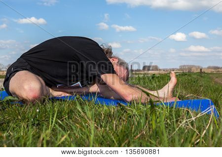 on an sunny day this man enjoys Janu Sirsasana yoga in nature