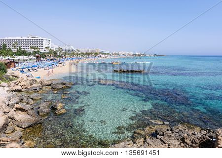 PROTARAS CYPRUS - JUNE 12 2016: Photo of sea and fig tree bay beach in protaras cyprus island with swimming people rocks and hotels at bank holidays