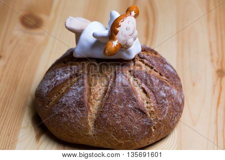Round loaf of homemade bread and cute angel porcelain figurine on wooden background