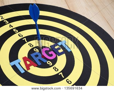 Word spell TARGET on dart board with blue arrow on wood background (Business Concept)