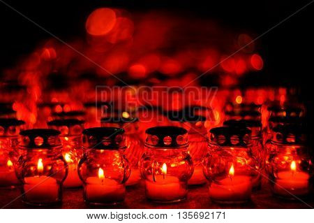 Many candles burning in red candle holders at night closeup