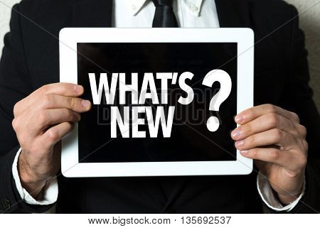 Business man holding tablet with the text: Whats New?