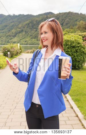 Beautiful young woman with mobile phone. Light bright setting. Busy girl student in motion with beverage cups in hand.