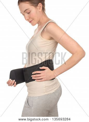 Woman putting on, wrapped, wears, suits, sports medical belt, corset on a white background, isolate