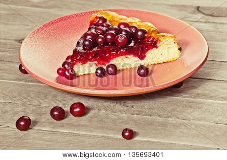 piece open pie with cranberries on a wooden table