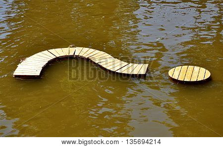 Detailed view of a wooden question mark in the river