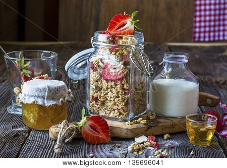 Ready-made granola with dried strawberries and almonds. Healthy breakfast with cereal muesli, dried and fresh strawberries, almonds, milk, honey, a simple wooden background in rustic style. selective focus