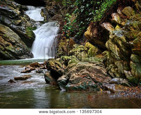 mountain waterfall with stones in moss and greenery