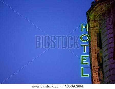 Glowing neon Hotel sign against clear evening sky