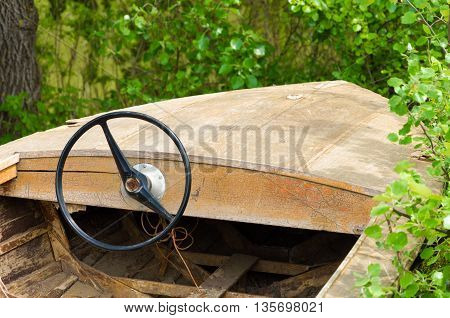 retro wooden boat with steering wheel. forest.