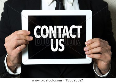 Business man holding tablet with the text: Contact Us