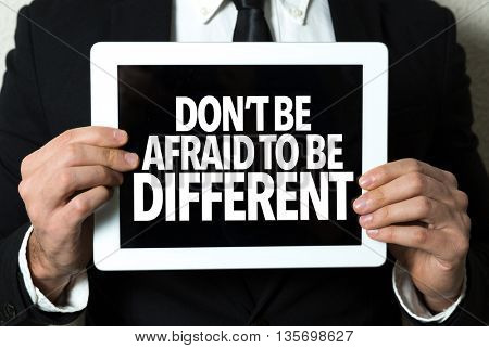 Business man holding tablet with the text: Don't Be Afraid to Be Different