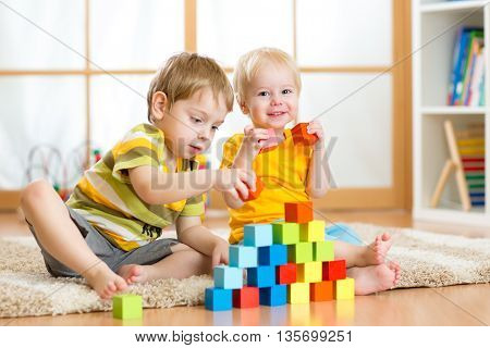 Preschooler children playing with colorful toy blocks. Kid playing with educational wooden toys at kindergarten or day care center. Toddler boys in nursery room.