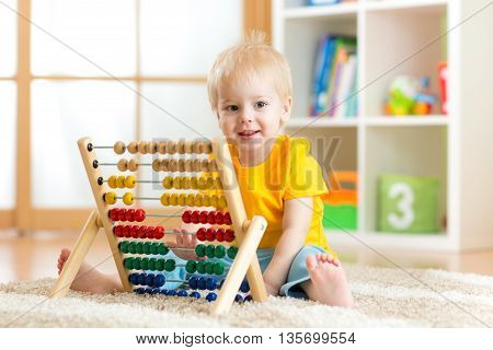 child boy smiling and playing with counter toy at home