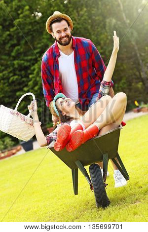 Picture of young couple having fun in the garden riding a barrow