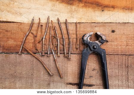 Pincers with rusted nails on timber background. DIY. Tools