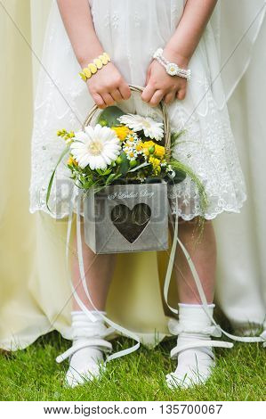 Flower girl holding her bouquet, wedding flowers.