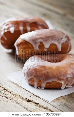 Fresh homemade donuts on a wooden table. Selective focus
