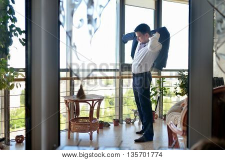 Groom is wearing a suit indoors. Male portrait of handsome guy. Beautiful model boy in colorful wedding clothes. Man is posing
