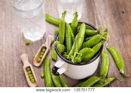 raw ripe fresh green peas in white cup with clear mineral water